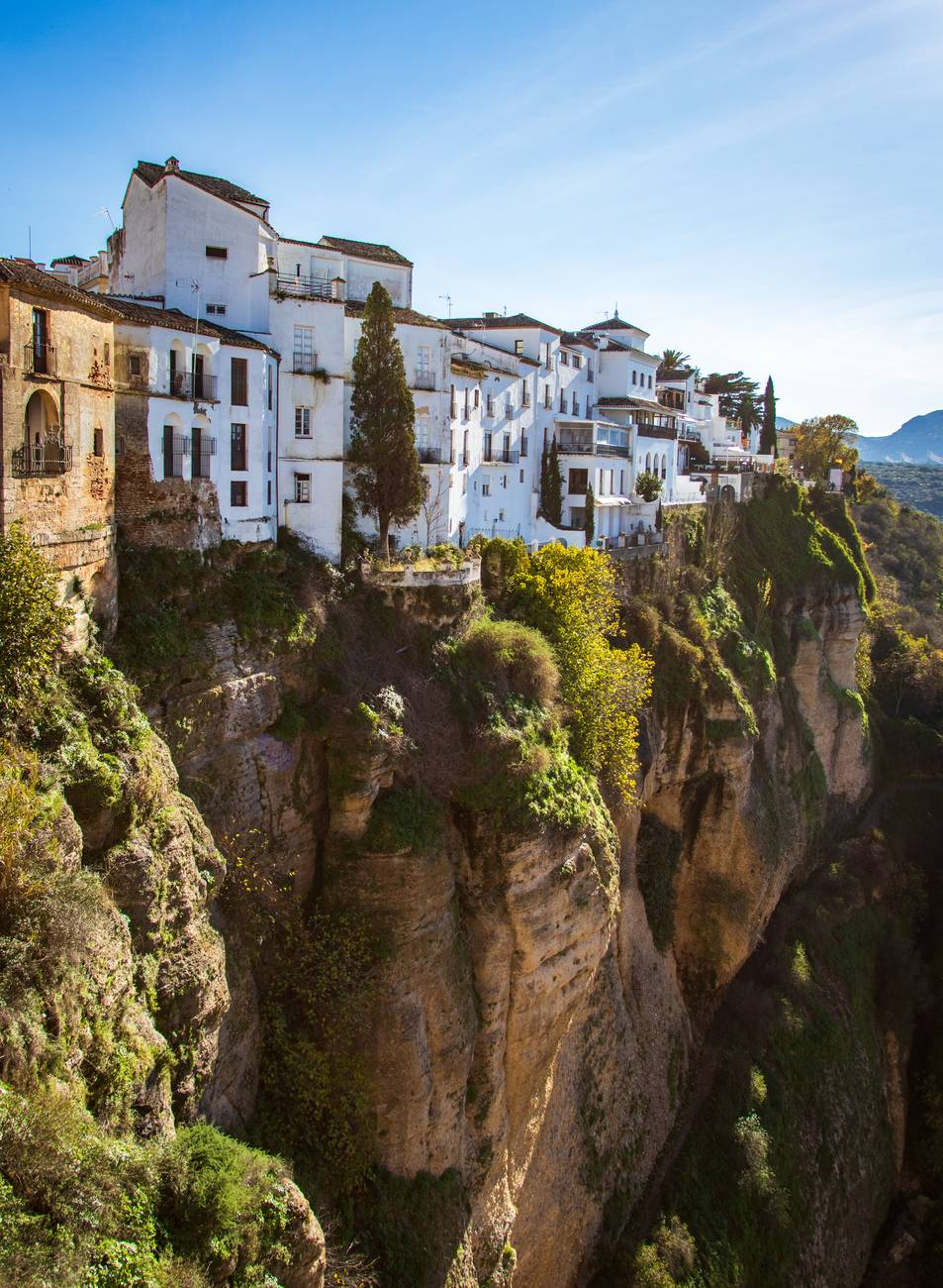white concrete buildings next to a cliff